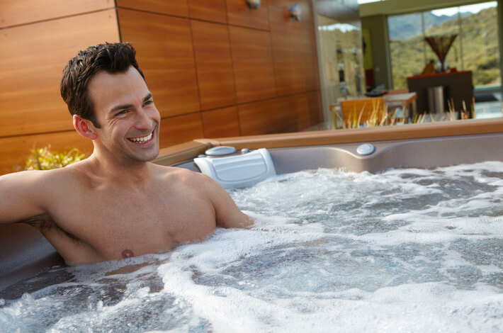 Man smiling and relaxing in a hot tub